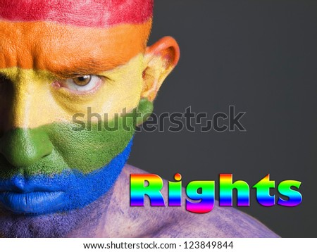 "Gay flag painted on the face of a man. Man is looking at camera and has a serious expression. The word ""rights"" is written. - stock photo"