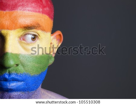 Gay flag painted on the face of a man. Man is looking sideways with restlessness expression. - stock photo