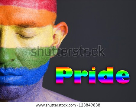 """Gay flag painted on the face of a man.The man's eyes are closed with a serene expression on his face. The word """"pride"""" is written at one side. - stock photo"""
