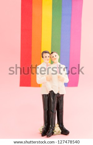 Gay groom cake toppers in front of rainbow flag on pink background - stock photo