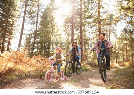 Gay Male Couple With Daughter Cycling Through Fall Woodland - stock photo