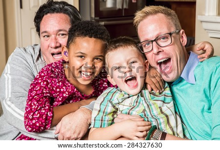 Gay parents pose with their childen in the living room - stock photo
