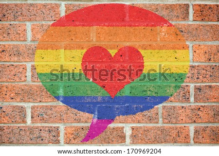 Gay pride colored speech bubble with red heart shape painted on old red brick wall - stock photo