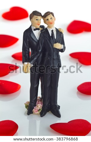 Gay wedding Cake Figurine with little velvet hearts as Background. - stock photo