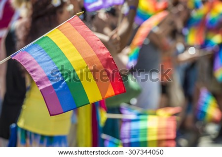 GayPride spectators carrying Rainbow gay flags during Montreal Pride March - stock photo