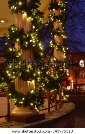 gazebo pillars wrapped with pine garlands and Christmas lights