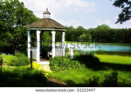 Gazebo situated by small town lake in a dreamy setting. - stock photo