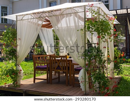 gazebo with wooden pergola and drapery - stock photo