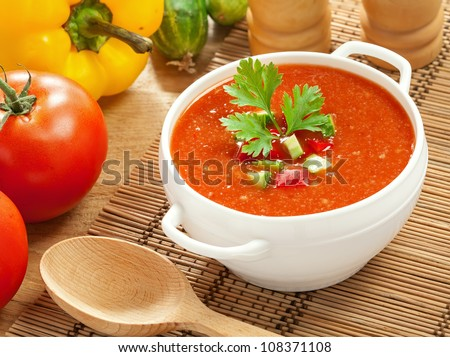 Gazpacho and ingredients on a table, vegetable soup - stock photo