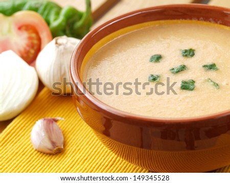 Gazpacho soup in ceramic brown bowl with raw ingredients, typical spanish cuisine - stock photo