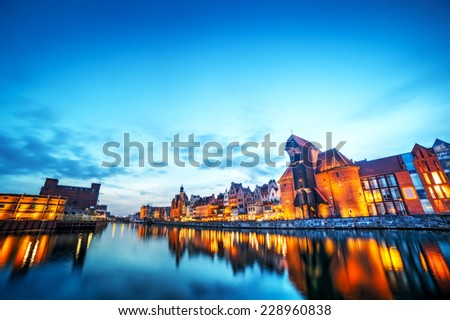 Gdansk old town and famous crane, Polish Zuraw. View from Motlawa river, Poland at romantic sunset, night. The city also known as Danzig and the city of amber. Sky copyspace - stock photo