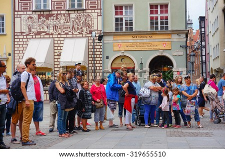 GDANSK, POLAND - JULY 29, 2015: Group of people looking at something in the city center - stock photo