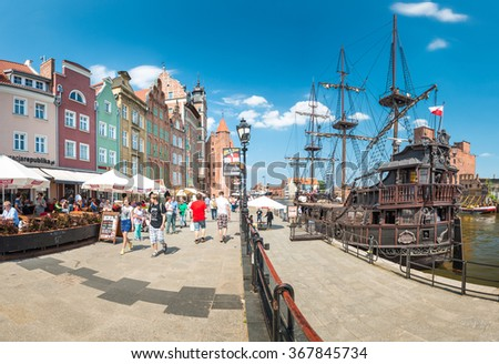 Gdansk, Poland - 18 May, 2013: City of Gdansk, Poland, Europe. Tourists walking street near Motlawa river with old ship . Sunny day with blue cloudy sky.