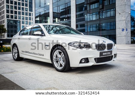 GDANSK, POLAND - SEPTEMBER 3 , 2015: New model BMW 520d in white against modern design buildings in Gdansk. BMW is a German automobile, motorcycle and engine manufacturing company founded in 1916. - stock photo