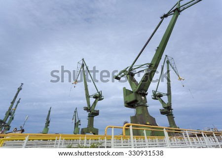 GDANSK, POLAND, SEPTEMBER 18: Outdoors view of the Stocznia Gdansk industrial massive cranes in shipyards with cloudy sky, Poland 2013