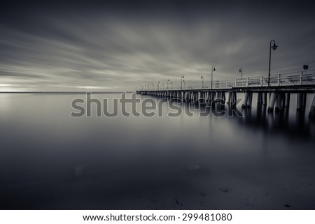 Gdynia Orlowo pier. Black and white photo of Baltic sea shore seascape. - stock photo