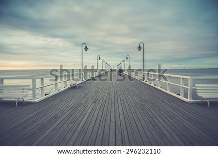 Gdynia Orlowo pier. Vintage photo of Baltic sea shore seascape.People while walking - stock photo