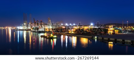GDYNIA, POLAND - MARCH 23: Gdynia city shipyard in panorama view in March 23, 2015 in Gdynia - Poland. Spring night panorama of shipyard cranes and boats under night work with water reflection.