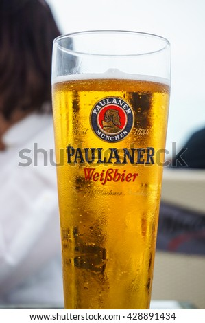 GDYNIA, POLAND - MAY 28, 2016: Cold fresh beer in a Paulaner Weissbier glass standing on table - stock photo