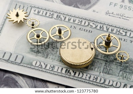 Gear of success.Gear wheels on dollar bill revealing the path to success - stock photo