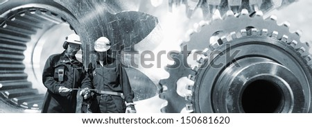 gears and cogwheel machinery with two engineers, workers in the foreground - stock photo
