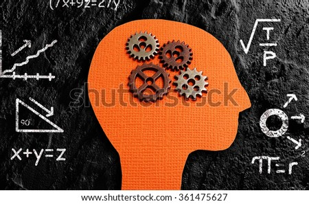 Gears and paper figure head with math formulas