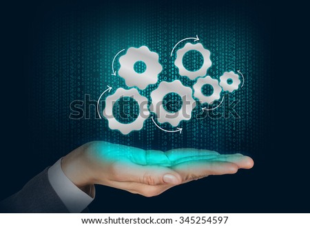 Gears mechanism floats on the human hand over digital background