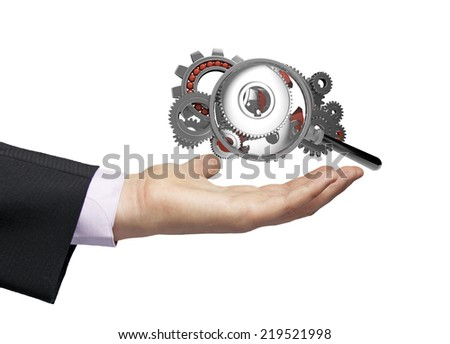 gears with gears and a magnifying glass over a businessman hand, operating analyzing concept - stock photo