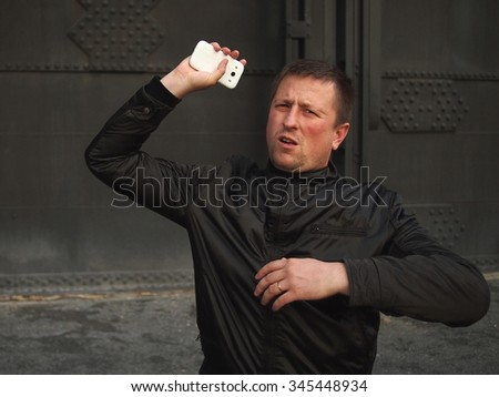 Ged rid of it! Man throwing away a smart phone. - stock photo