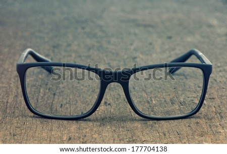Geek eyeglasses laying on a grungy wooden background