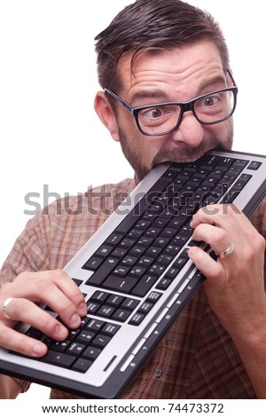 Geek is hysterically biting the keyboard - stock photo