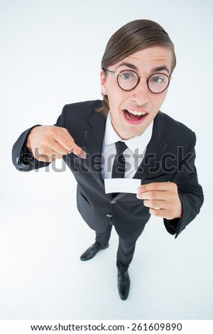 Geeky businessman looking at camera and pointing at card on white background - stock photo