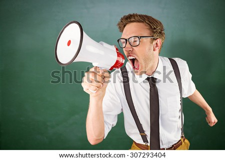 Geeky businessman shouting through megaphone against green chalkboard - stock photo