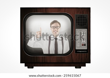 Geeky businessman smiling and pointing against retro tv