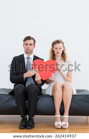Geeky couple sitting on couch on white background