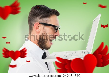 Geeky frustrated businessman looking at his laptop against green vignette - stock photo