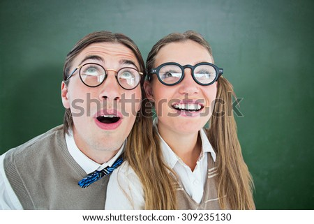 Geeky hipster couple raising eyes against green chalkboard