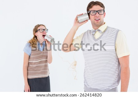 Geeky hipster couple speaking with tin can phone on white background - stock photo