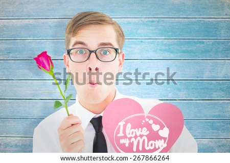 Geeky hipster holding a red rose and heart card against wooden planks - stock photo