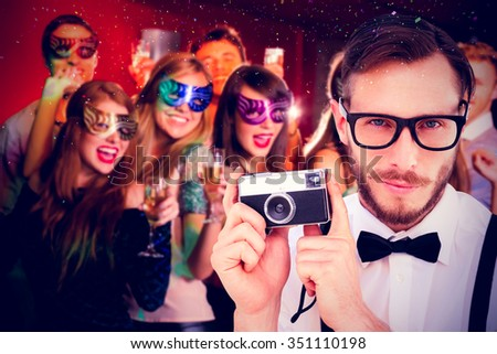 Geeky hipster holding a retro camera against friends in masquerade masks drinking champagne - stock photo