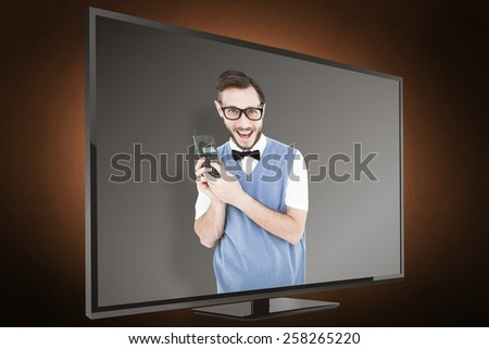 Geeky hipster holding a retro cellphone against orange background with vignette - stock photo
