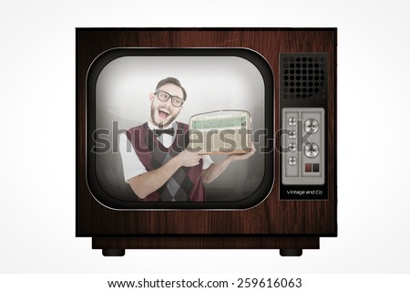 Geeky hipster holding a retro radio against retro tv