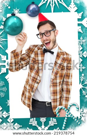 Geeky hipster in party hat pointing against christmas frame - stock photo