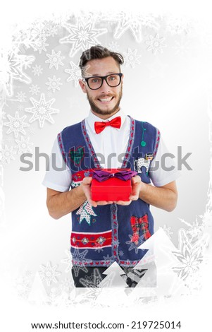 Geeky hipster offering christmas gift against christmas frame - stock photo