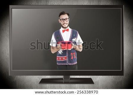 Geeky hipster offering christmas gift against grey vignette - stock photo