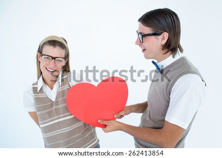 Geeky hipster offering red heart to his girlfriend on white background - stock photo