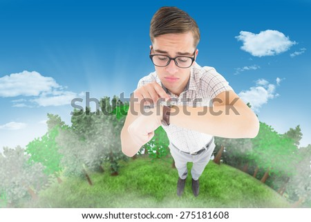 Geeky hipster pointing to his watch against blue sky - stock photo