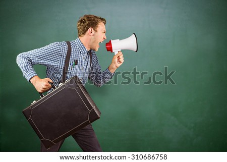 Geeky hipster shouting through megaphone against green chalkboard - stock photo