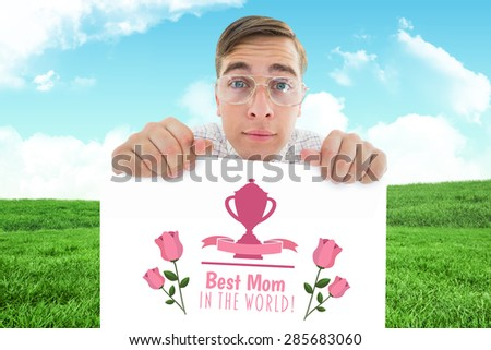 Geeky hipster smiling and showing card against field and sky - stock photo
