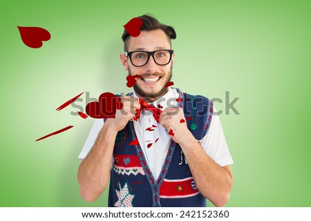 Geeky hipster wearing christmas vest against green vignette - stock photo